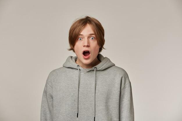 Portret van geschokt, verbaasd mannetje met blond haar. grijze hoodie dragen. mensen en emotie concept. verbijsterd door wat hij ziet. kijken verbaasd geïsoleerd over grijze muur