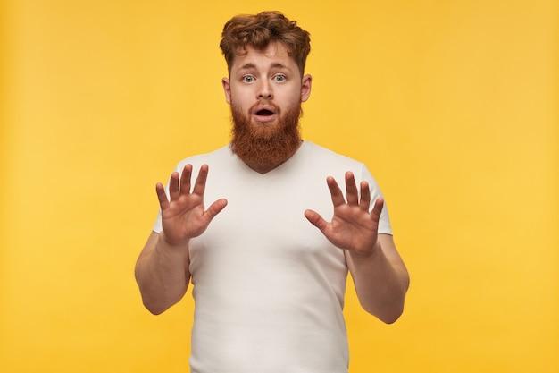 Portret van geschokt verbaasde jonge man met een grote baard, draagt een leeg t-shirt, toon stop gebaar met zijn handpalmen