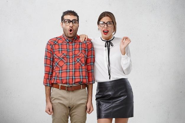 Portret van geschokt verbaasde jonge vrouw en man in bril, formele kleding ontdekt onaangenaam of vreselijk nieuws