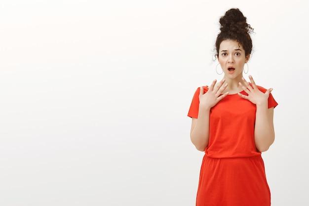 Portret van geschokt verbijsterd aantrekkelijke europese vrouw in casual rode jurk, hijgend met geopende mond