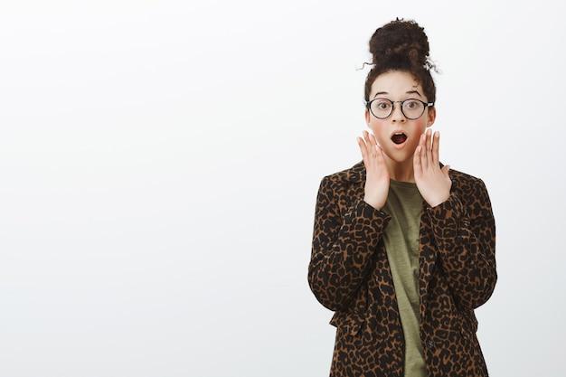Portret van geschokt verrast vriendin in luipaardjas en zwarte trendy bril, kaak laten vallen, wauw zeggen en palmen vasthouden in de buurt van mond