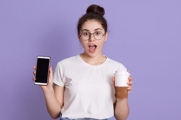 Portret van geschokt verrast vrouw met donker haar, met meenemen koffiekopje en mobiele telefoon