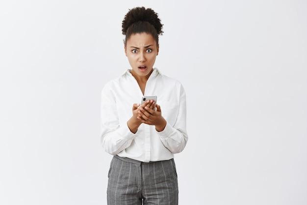 Portret van geschokt, verward en ontevreden knappe afro-amerikaanse vrouw in pak, smartphone vasthoudend en verbaasd starend, teleurgesteld met rare boodschap over grijze muur