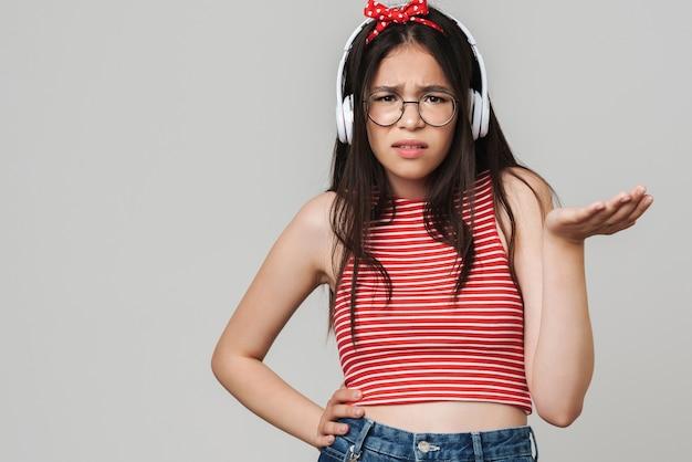 Portret van geschokt verward jong ontevreden tienermeisje gekleed in fel rood t-shirt luisteren muziek geïsoleerd over grijze muur.