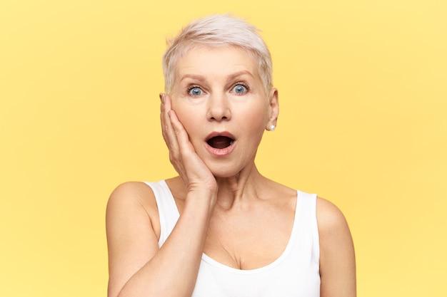 Portret van geschokt volwassen europese vrouw die naar adem snakt met geopende mond, verrast, hand op de wang houdt, iets belangrijks vergeten, verward gefrustreerde gezichtsuitdrukking