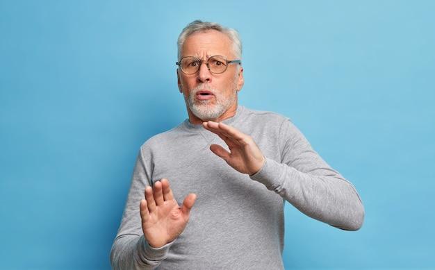 Portret van geschokt volwassen man met grijs haar en baard maakt bang gebaar probeert zichzelf te verdedigen draagt een transparante bril en casual trui bedekt zichzelf tegen agressie