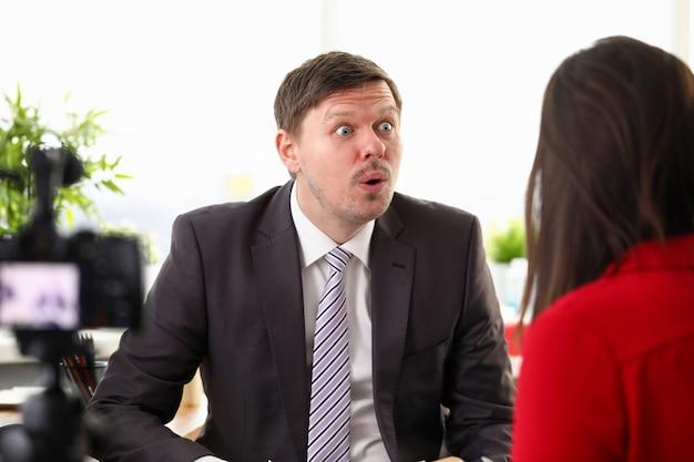 Portret van geschokt zakenman spreken met werknemer over zakelijke deal.