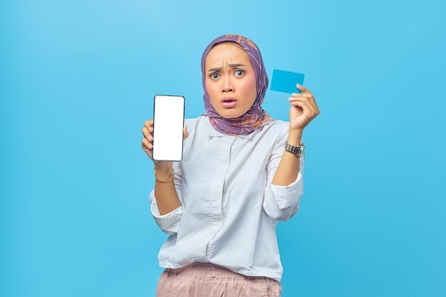 Portret van geschokte aziatische vrouw met creditcard en smartphone