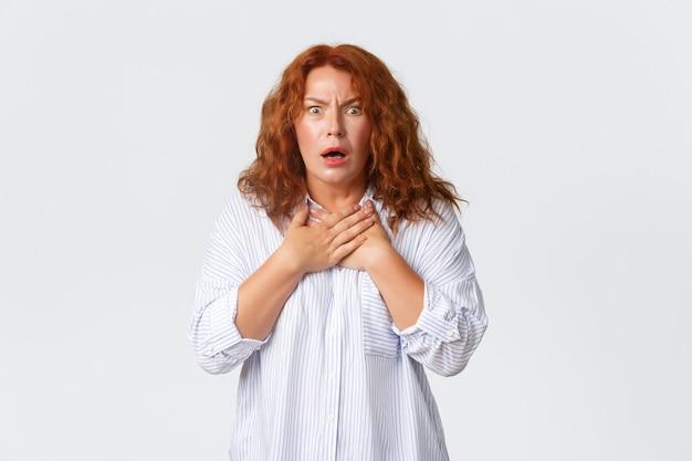 Portret van geschokte en bezorgde, geschrokken vrouw van middelbare leeftijd die in een hinderlaag wordt gelokt