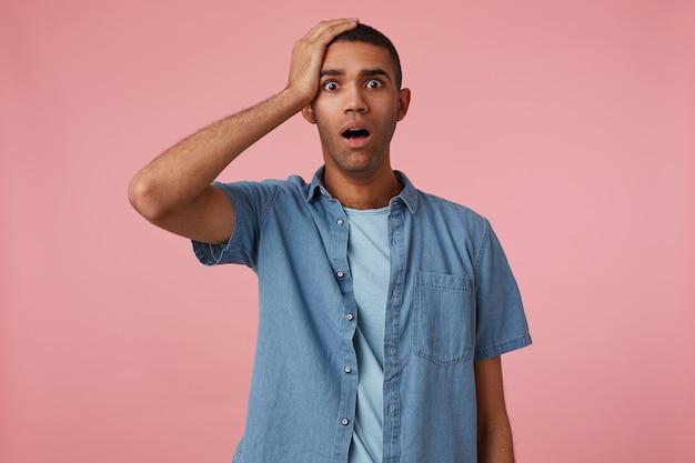 Portret van geschokte jonge aantrekkelijke donkere man in geruit overhemd, met vuisten omhoog en wijd open mond, zijn favoriete team miste een doelpunt, staat op een roze achtergrond en houdt zijn hoofd vast.