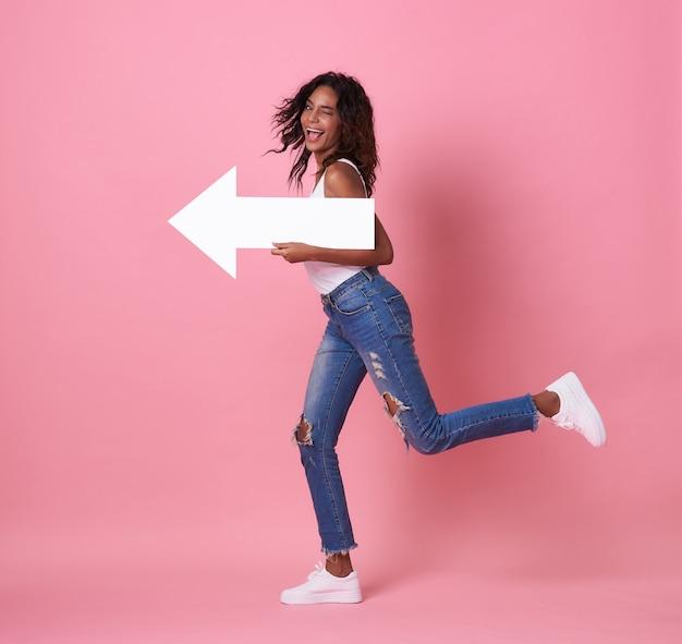 Portret van geschokte jonge afrikaanse vrouw die met haar pijl springen die op exemplaarruimte richten die over roze bannerachtergrond wordt geïsoleerd.