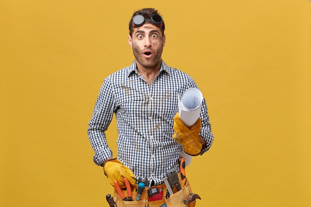 Portret van geschokte klusjesman met geruit overhemd, beschermende brillen en handschoenen, gereedschapsriem met opgerold papier met verbaasde uitdrukking die zijn fout realiseert. mensen en werkconcept