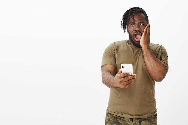 Portret van geschokte man in een bruin t-shirt poseren tegen de witte muur met zijn telefoon