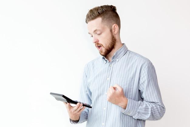 Portret van geschokte man op zoek naar rekenmachine