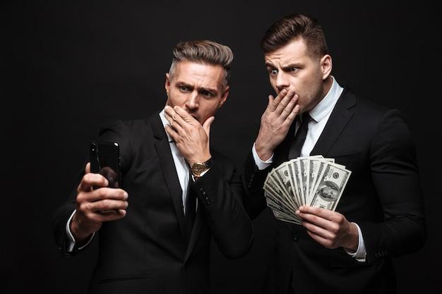 Portret van geschokte twee zakenlieden gekleed in een formeel pak met mobiele telefoon en geldbankbiljetten geïsoleerd over zwarte muur
