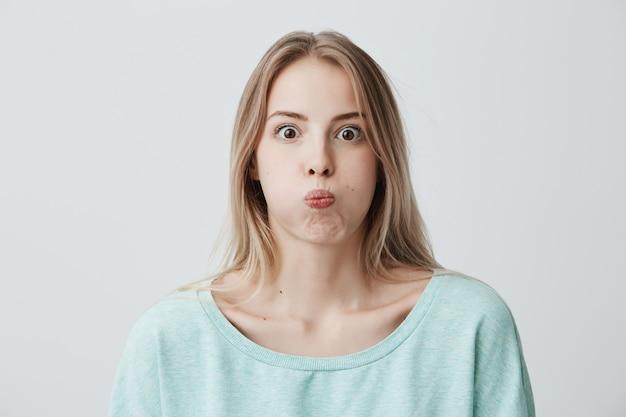 Portret van geschokte, verbaasde jonge blonde vrouw met terloops geklede ogen, pruilend op haar wangen, alsof ze vol water zitten en weigert geheim te vertellen. gezichten kaukasisch vrouwelijk model maken.