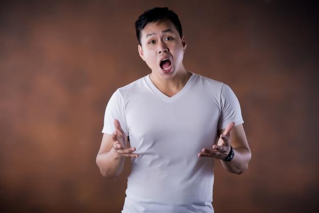 Portret van geschokte verbluft verrast jonge man ogen en mond wijd open