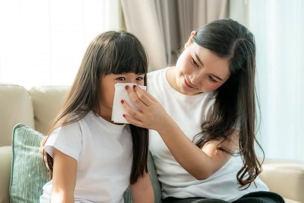 Portret van gesneden aziatisch meisje die snot blazen in het servet