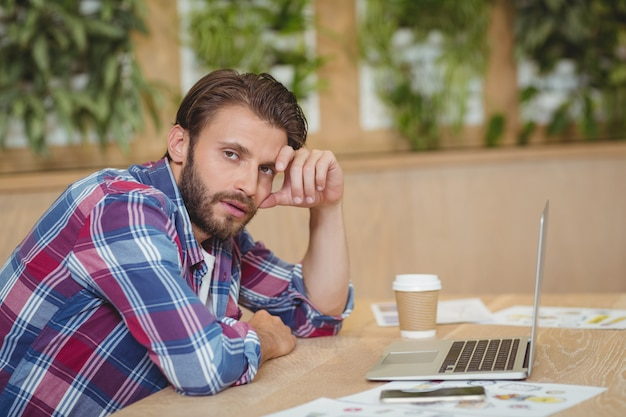 Portret van gespannen directeur met laptop die bij bureau situeert