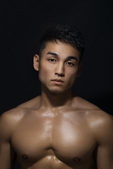 Portret van gespierde aziatische man binnenshuis in de studio