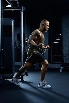 Portret van gespierde bebaarde bodybuilder die lage kabeloversteekoefening doet.