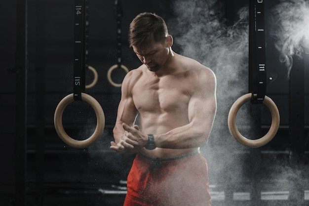 Portret van gespierde crossfit atleet handen klappen en voorbereiden op training in de sportschool