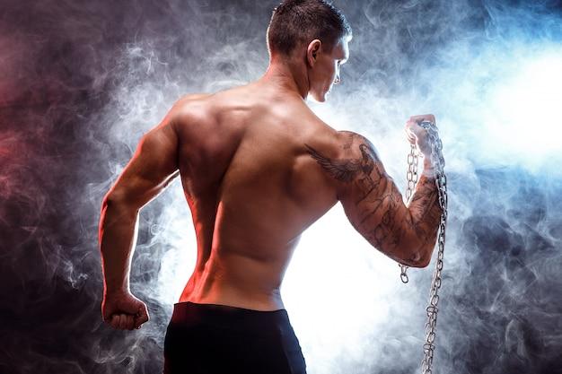 Portret van gespierde getatoeëerde sportman met metalen ketting. scène met rook