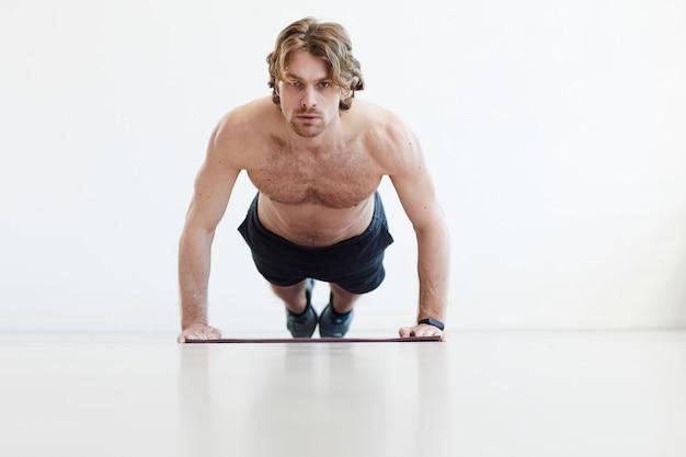 Portret van gespierde jonge man doet push-ups geïsoleerd op een witte achtergrond
