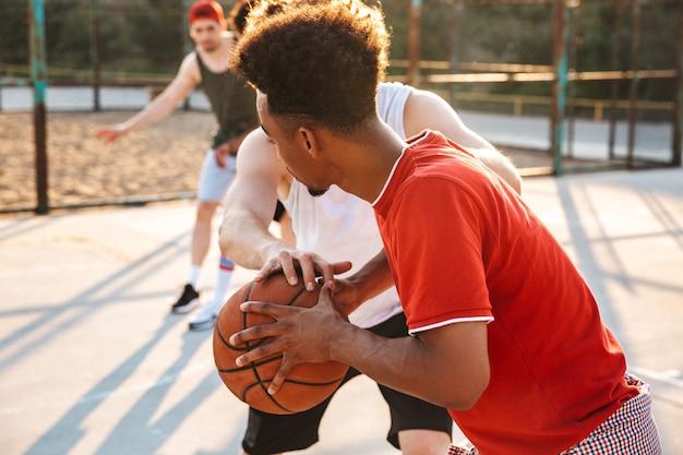 Portret van gespierde sportieve jongens spelen basketbal op de speelplaats buiten, tijdens zonnige zomerdag