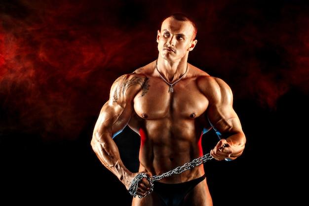 Portret van gespierde sportman met metalen ketting op nek. zwart met rook