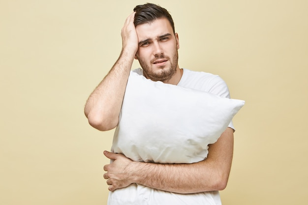 Portret van gestresste jonge brunette man die lijdt aan hoofdpijn, hand op zijn hoofd houden en kussen vasthouden, kan niet in slaap vallen zonder slaappillen, na depressieve gefrustreerde gezichtsuitdrukking
