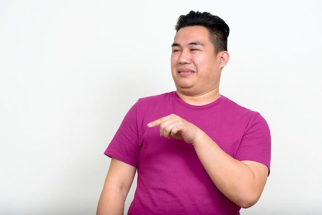 Portret van gestresste jonge overgewicht aziatische man wijzende vinger en walgt op zoek
