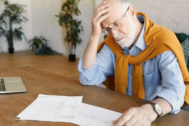 Portret van gestrest boos volwassen blanke zakenman in formele kleding en bril zit open laptop, documenten bestuderen, financiële problemen onder ogen zien, hand op zijn kale hoofd houden