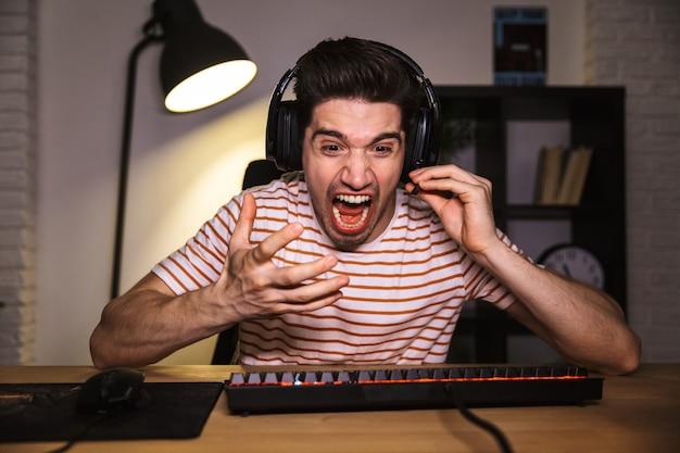 Portret van gestrest jongeman 20s met hoofdtelefoon schreeuwen, zittend aan een bureau in de kamer en het spelen van videogames