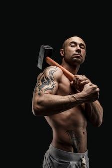 Portret van getatoeëerde shirtless atleet met hamer op schouder