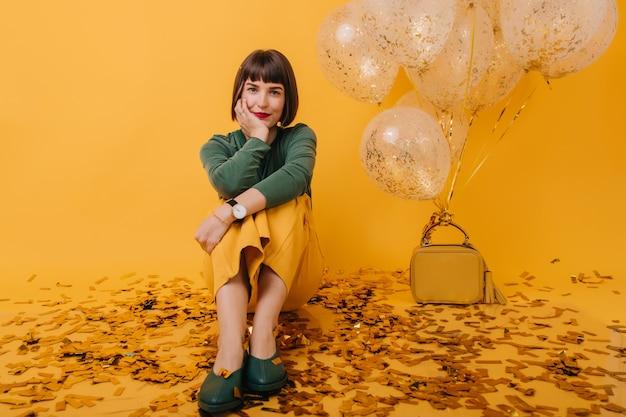 Portret van geweldige jonge vrouw met kort haar, zittend op sparkle confetti. indoor foto van enthousiast vrouwelijk model in groene trui poseren na feest.