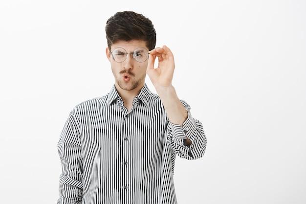 Portret van gewone volwassen europese mannelijke student, bril opstijgen en glas brillen schoonmaken, gericht naar bril staren, lippen vouwen om te blazen, staande over grijze muur