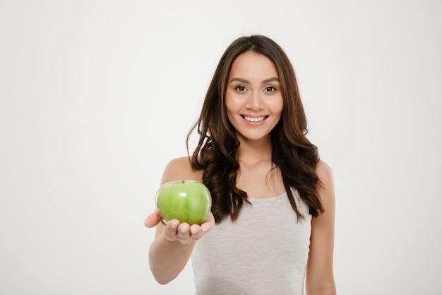 Portret van gezonde mooie vrouw die en groene sappige appel op camera glimlacht toont, die over wit wordt geïsoleerd