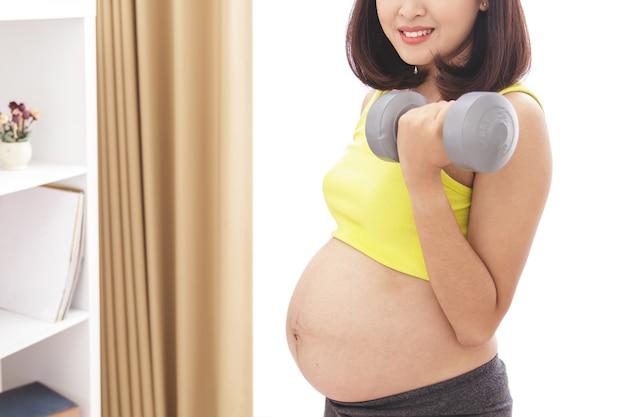 Portret van gezonde zwangere vrouw uitoefenen met behulp van halters close-up
