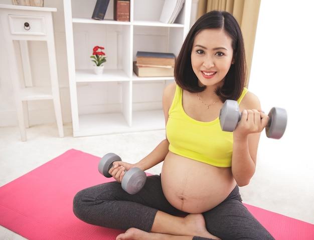 Portret van gezonde zwangere vrouw uitoefenen met behulp van halters thuis