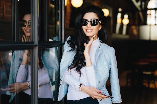 Portret van glamour jonge vrouw met donker golvend haar dat zonnebril en witte blouse met elegant jasje draagt