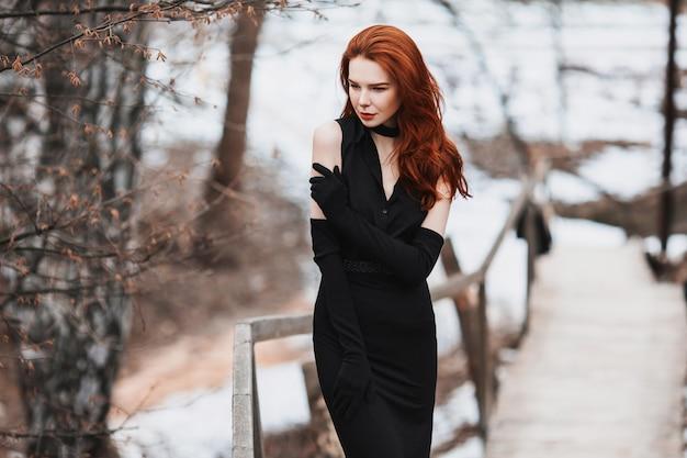 Portret van glamoureuze meisje met lang rood haar in zwarte kleding. vrouw in zwarte kleding en lange zwarte handschoenen die op een achtergrond van de winter, de herfstaard stellen. vrouwelijke streetstyle. prachtig elegant model