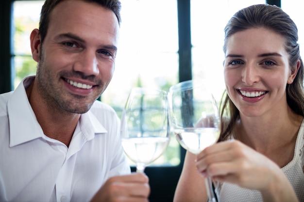 Portret van glazen van de paar de roosterende wijn bij eettafel