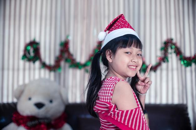 Portret van glimlach klein kindmeisje in een kerstmuts