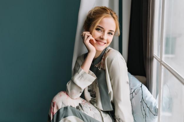 Portret van glimlachen, gelukkig blond meisje naast het raam, ontspannen in de ochtend, goede tijd thuis. ze is gekleed in een mooie zijden pyjama.