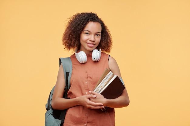 Portret van glimlachend afrikaans-amerikaans studentenmeisje met koptelefoon rond de nek met boeken en tas op rug tegen lichte achtergrond