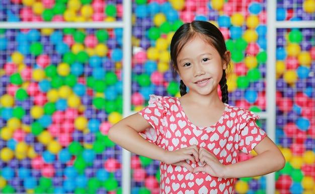 Portret van glimlachend aziatisch meisje die hartteken tonen tegen kleurrijke balspeelplaats. drukt liefde-emoties uit.
