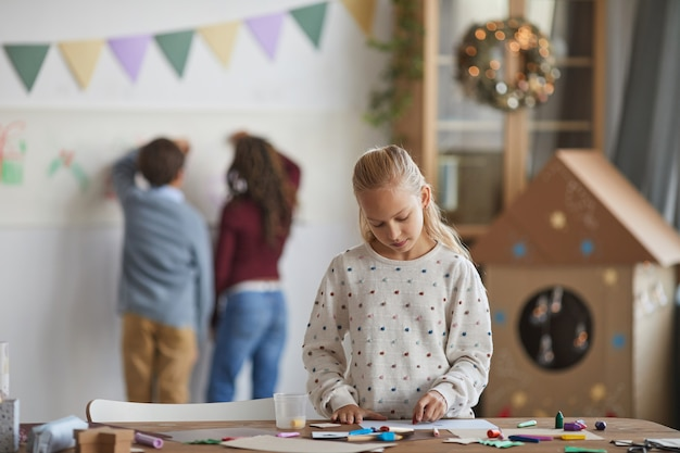 Portret van glimlachend blond meisje permanent door tafel te maken en te genieten van kunstles op school, kopie ruimte
