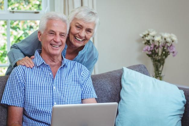 Portret van glimlachend gepensioneerd paar dat laptop met behulp van