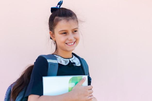 Portret van glimlachend kind meisje klaar voor school, een map in handen houden, rugzak op roze dragen
